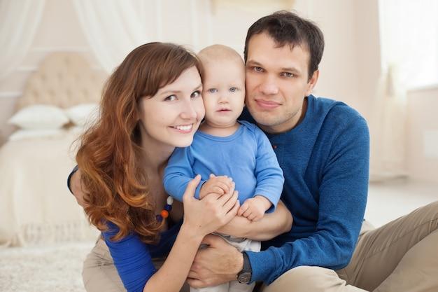 Familia feliz con bebé jugando en la alfombra