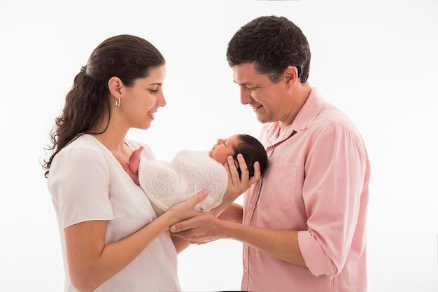 Familia feliz con bebé recién nacido sobre una superficie blanca.