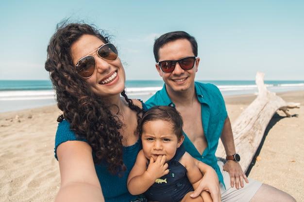 Familia feliz con el bebé tomando selfie en la playa en día de verano