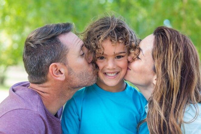 Familia feliz besando a la cámara en el parque en un día soleado