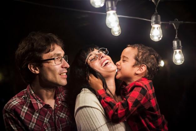 Familia feliz bajo bombillas sesión de fotos de navidad