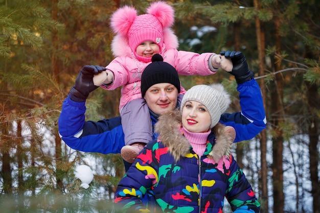 Familia feliz en el bosque de invierno. pasar tiempo al aire libre en invierno