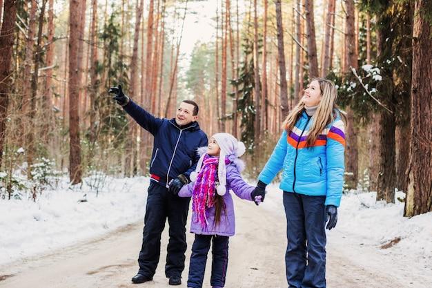 Familia feliz en bosque de invierno