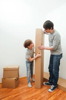 Familia feliz con cajas de cartón en casa nueva en el día de la mudanza. día de la casa móvil y concepto de bienes raíces. los sueños se hacen realidad.