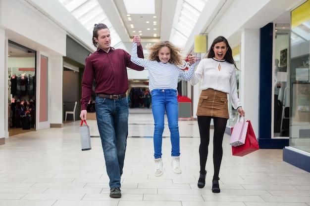 Familia feliz caminando con bolsas de compras