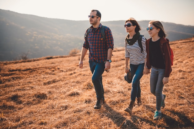 Familia feliz caminando juntos en una montaña