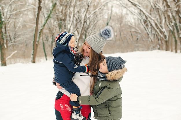 Familia feliz caminando en el parque de invierno. madre con niños divirtiéndose en invierno.