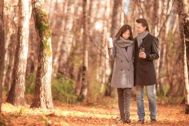 Familia feliz caminando en el parque otoño en día soleado de otoño