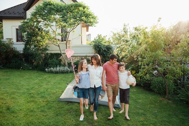 Familia feliz caminando sobre la hierba en frente de la tienda al aire libre