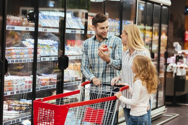 Familia feliz con carrito de compras en supermercado