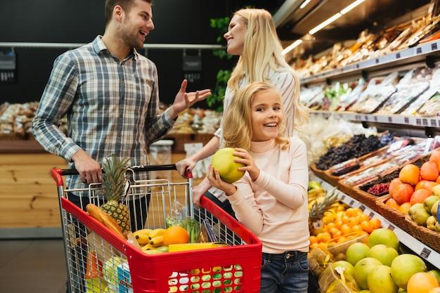 Familia feliz con carrito de compras