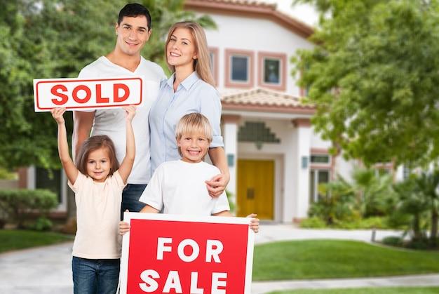 Familia feliz con cartel de venta