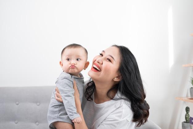 Familia feliz en casa. madre sosteniendo a su hija en la sala de estar en la acogedora mañana de fin de semana