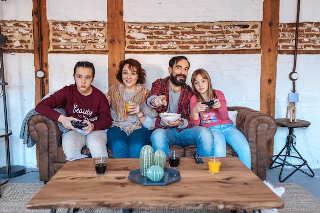 Familia feliz en casa viendo películas en el sofá y comiendo palomitas de maíz