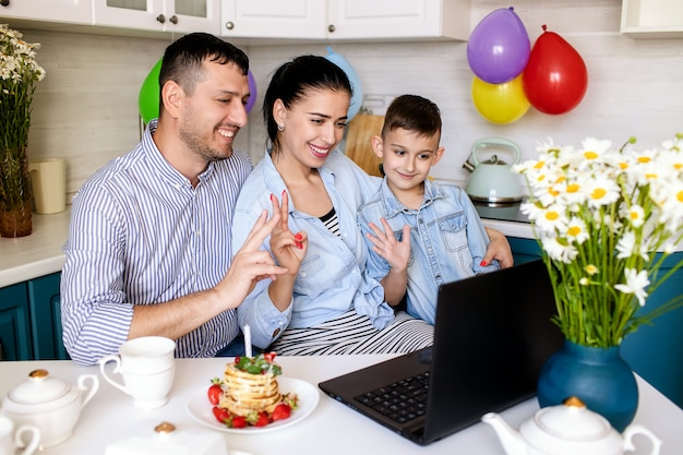 Familia feliz celebrando un cumpleaños en casa en la cocina y chateando en línea en una computadora portátil