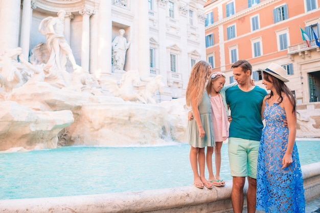 Familia feliz cerca de fontana di trevi con mapa de la ciudad
