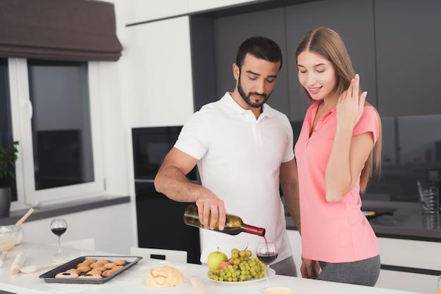 Familia feliz en la cocina. beber vino concepto.