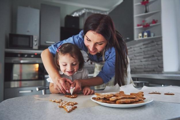 Familia feliz en la cocina. concepto de comida de vacaciones. madre e hija decoran galletas. familia feliz en la fabricación de pasteles caseros. comida casera y pequeño ayudante