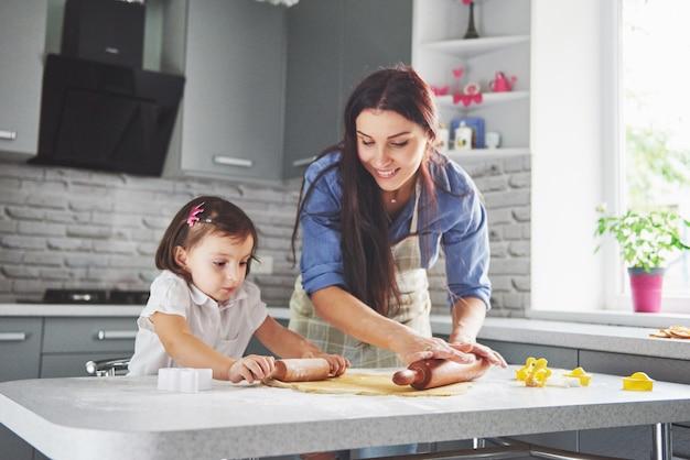 Familia feliz en la cocina. concepto de comida de vacaciones. madre e hija preparando la masa, hornear galletas. familia feliz en hacer galletas en casa. comida casera y pequeño ayudante