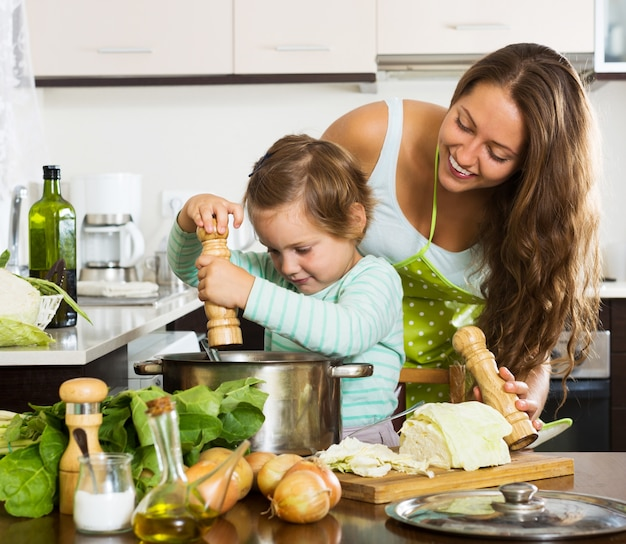 Familia feliz cocinando sopa