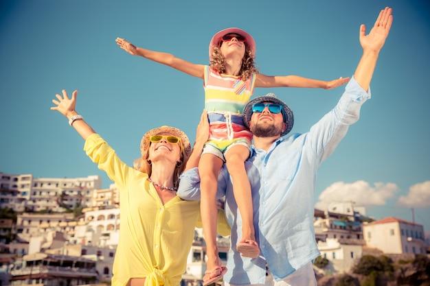 Familia feliz con coloridas gafas de sol y sombreros con una ciudad europea de fondo