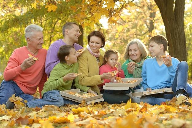 Familia feliz comer pizza juntos en el parque otoño