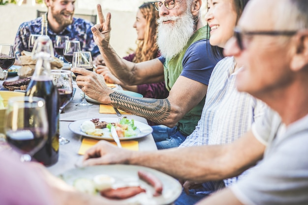 Familia feliz comiendo y bebiendo vino en la cena de barbacoa en backyar al aire libre