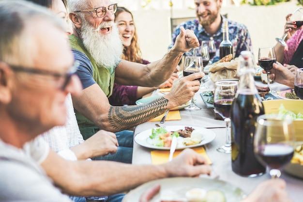 Familia feliz comiendo y bebiendo vino en la cena de barbacoa en el patio al aire libre