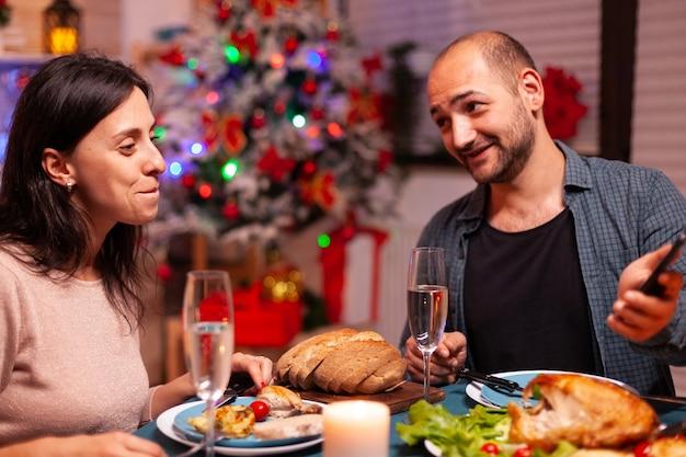 Familia feliz comiendo una deliciosa cena sentado en la mesa de comedor
