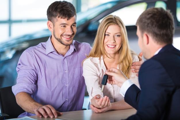 Familia feliz con concesionario de automóviles en el salón del automóvil o salón comprar un automóvil