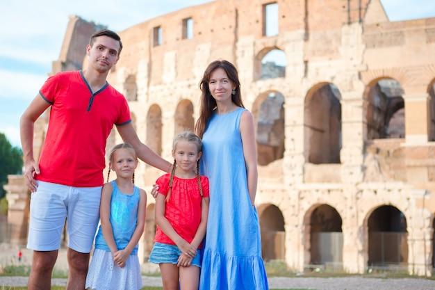 Familia feliz de cuatro en vacaciones italianas en el fondo del coliseo en roma