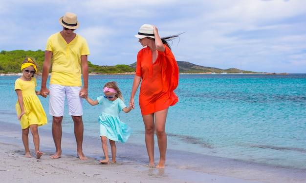 Familia feliz de cuatro en vacaciones en la playa
