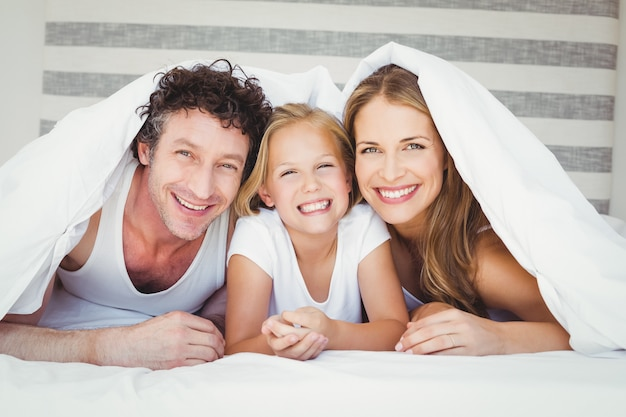 Familia feliz cubierta con edredón
