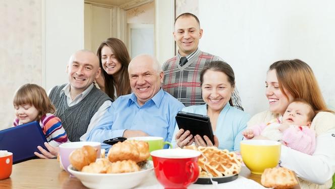 Familia feliz de tres generaciones con dispositivos electrónicos