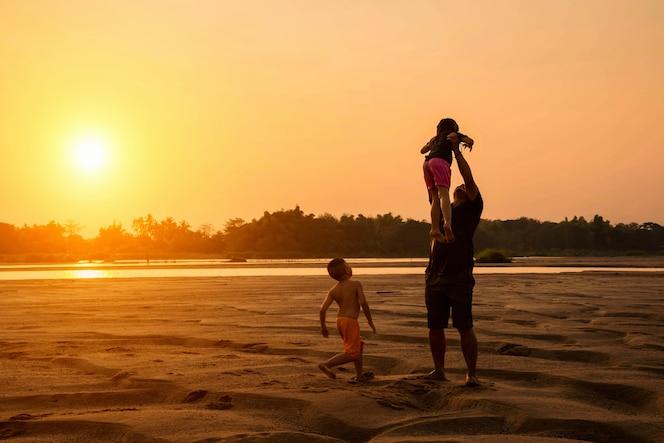 Familia feliz de tres personas, padre, hijo e hija en la playa en el cielo al atardecer.