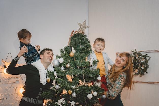 Familia feliz decorando el árbol de navidad juntos