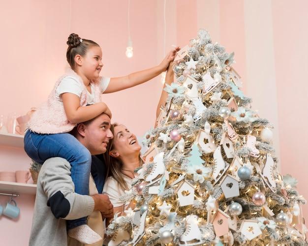 Familia feliz decorando el árbol de navidad