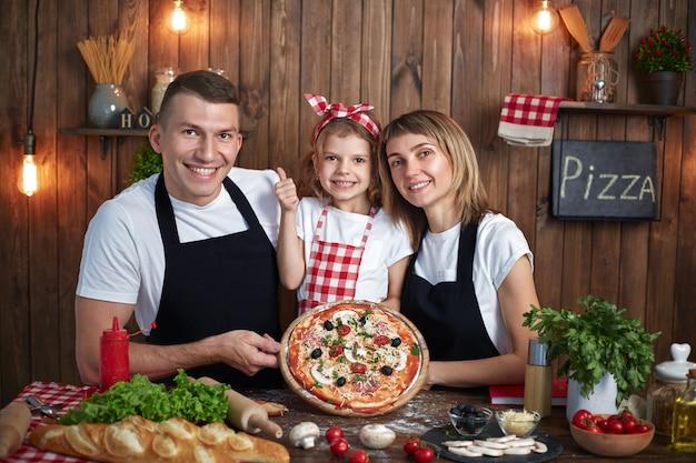 Familia feliz en delantales sonriendo y sosteniendo pizza cocinada