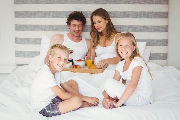 Familia feliz desayunando en la cama