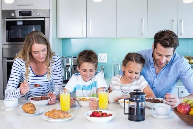 Familia feliz desayunando juntos en casa en la cocina