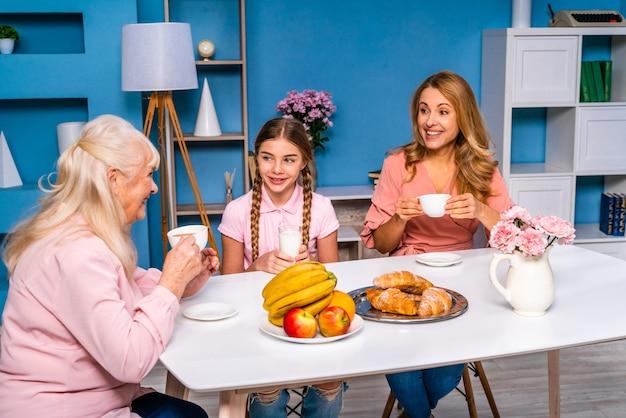 Familia feliz desayunando por la mañana en casa
