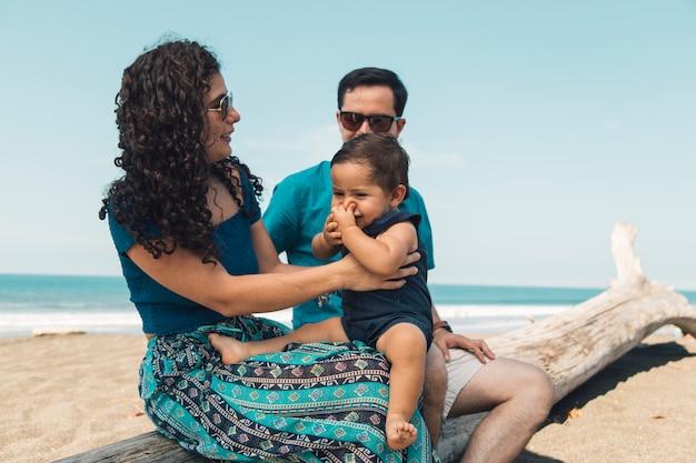 Familia feliz descansando en la orilla del mar