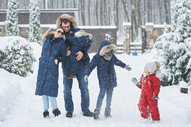 Familia feliz divertirse afuera cerca de la casa en invierno