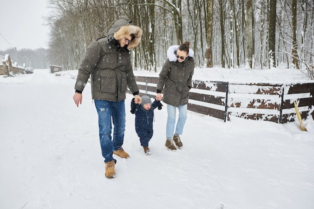 La familia feliz se divierte afuera cerca de la casa en invierno. vacaciones familiares y concepto de tiempo feliz