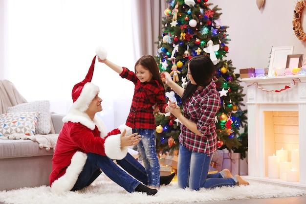 Familia feliz diviértete en la sala de navidad decorada