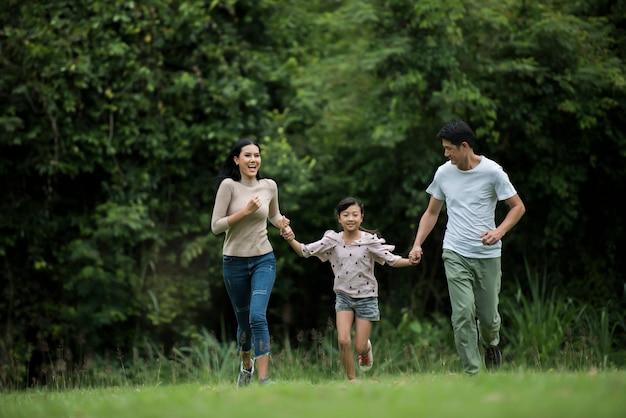 La familia feliz se está divirtiendo madre, padre e hija se están ejecutando en el parque.