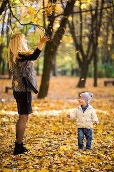 Familia feliz divirtiéndose al aire libre en el parque de otoño contra hojas borrosas