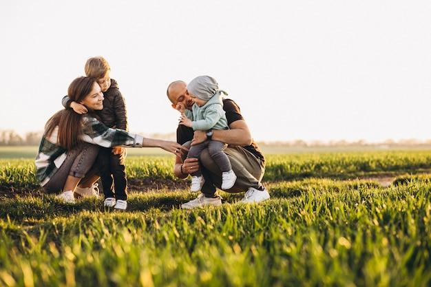 Familia feliz divirtiéndose en el campo en la puesta del sol