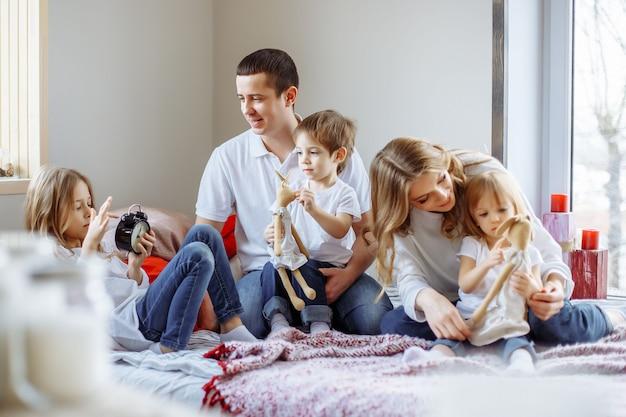 Familia feliz divirtiéndose juntos en casa en el dormitorio