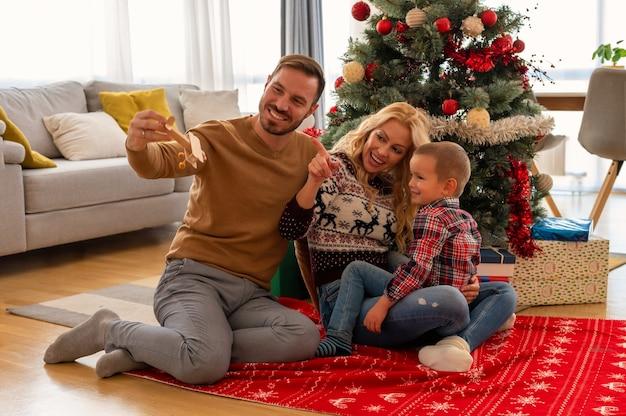 Familia feliz divirtiéndose y posando junto al árbol de navidad